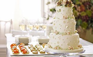 A beautiful three tiered wedding cake and macarons