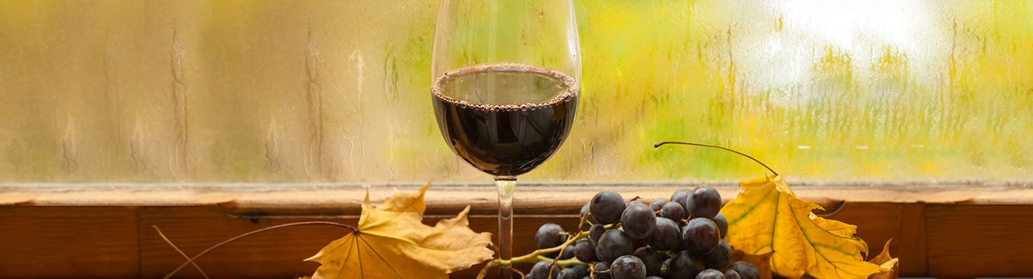 A glass of red wine infront of a rain specked window surrounded by leaves and grapes