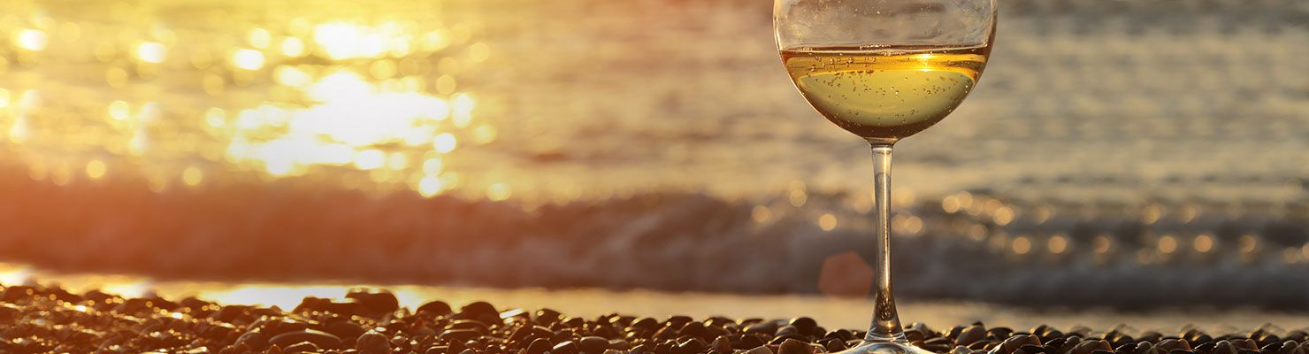 A glass of white wine in front of a sunset