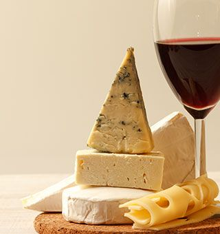 Cheese on a board and a glass of Red wine
