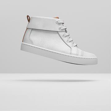Vista lateral de unas botas blancas de cuero, elevadas por encima del suelo