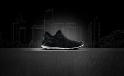 Black trainer boot on a smooth concrete surface with a monochrome illustrative background showing a skyline