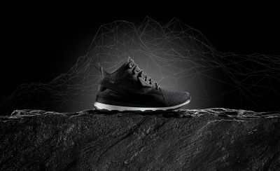 Black trainer boot on a concrete surface with an monochrome illustrative background showing a mountain range