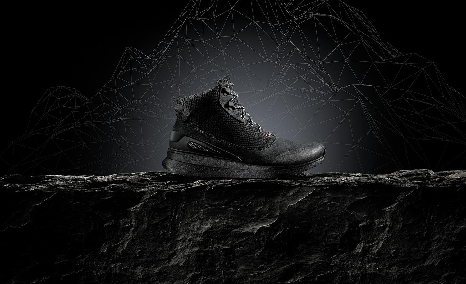 Black walking boot on a textured surface with a monochrome illustrative mountain range background