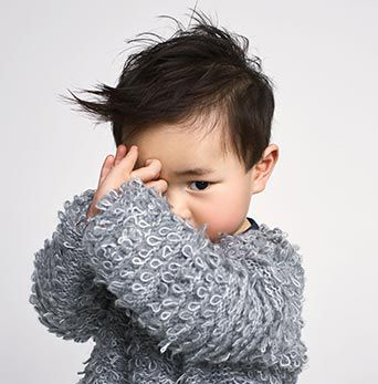 A young child, covering his face, wearing a grey cardigan