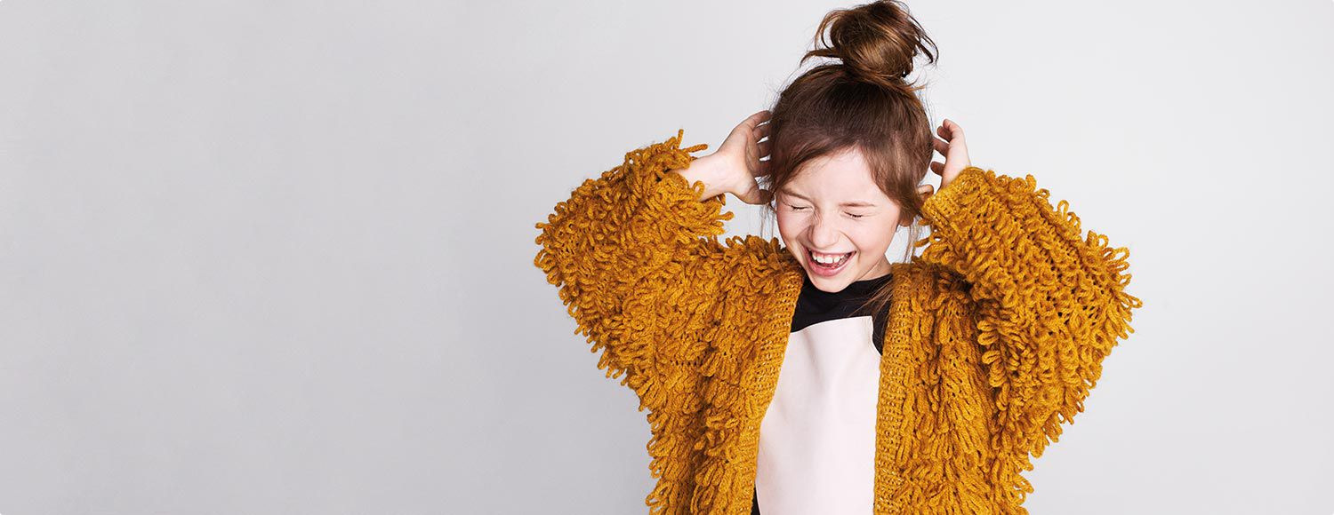 A girl wearing a yellow cardigan
