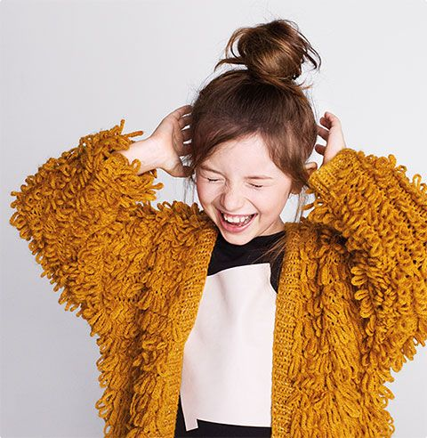 An image of a girl wearing a yellow cardigan