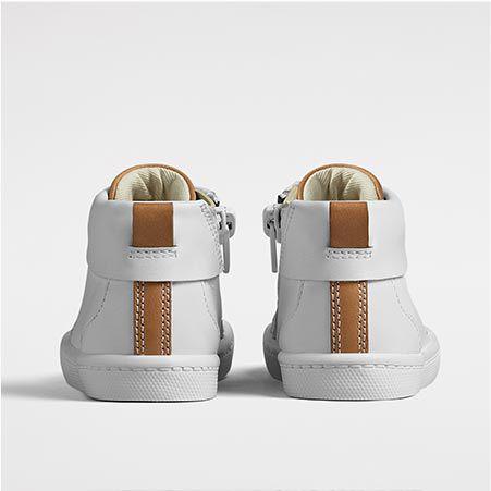 Plan rapproché de l'arrière d'une paire de baskets blanches avec des détails en cuir marron