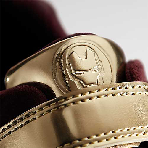 Close up shot of  Iron Man's Tri Hero golden badge, select this box to see a larger image