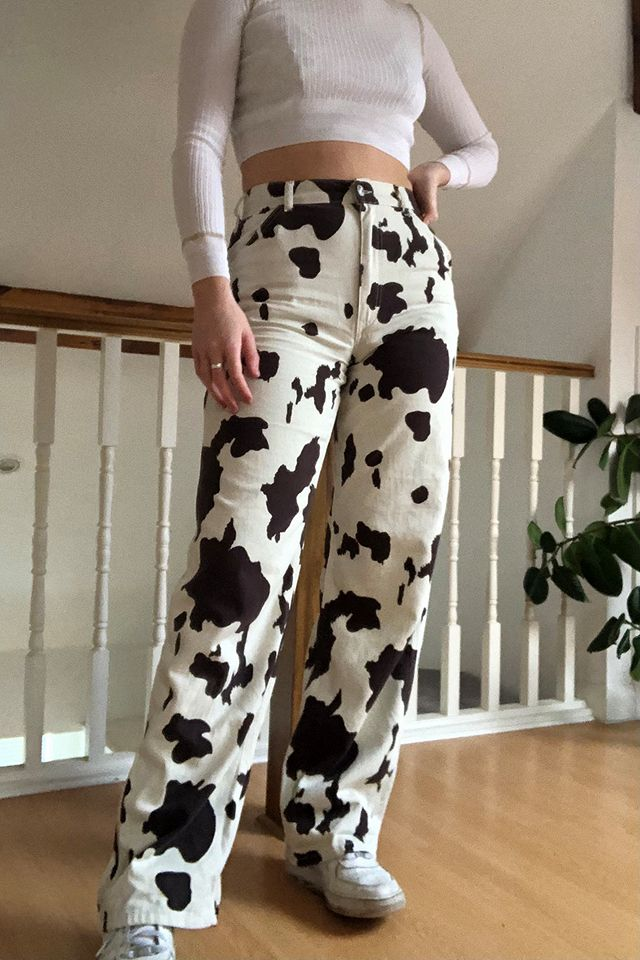 Woman wears white long-sleeved crop top, cow print mom jeans and trainers.