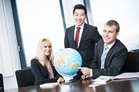 Drei HOFER Regionalverkaufsleiter sind in einem Büro und zeigen auf einen Globus auf dem Tisch.