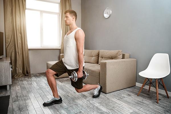 Mann in kurzen schwarzen Hosen betreibt in einem kleinen Wohnzimmer Hantelübungen mit Ausfallschritt.