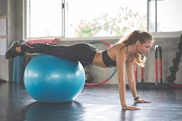 Frau liegt auf einem türkisen Gymnastikball und hat die Hände auf dem Boden, während der Körper gerade gestreckt ist.