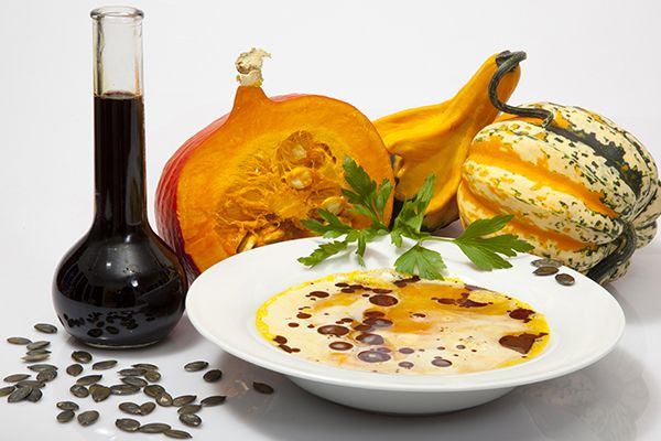 Eine Kürbiscremesuppe mit Kürbiskernöl in einem Suppenteller. Dahinter drei Kürbisse und eine Flasche Kürbiskernöl.