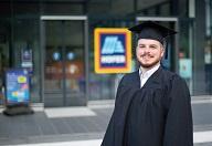 Ein Student in klassischem Absolventenoutfit steht vor einer HOFER Filiale, die verschwommen im Hintergrund zu erkennen ist.