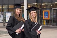 Zwei Masterabsolventinnen in klassischer Kluft mit Haube und Abschlussdokumenten in der Hand lächeln in die Kamera.