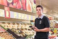 Junger HOFER Lehrling steht vor der Obst- und Gemüseabteilung und lächelt in die Kamera.