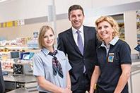 Ein Geschäftsführer und zwei HOFER Mitarbeiterinnen lächeln freundlich vor der Kasse in die Kamera.
