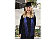 Masterabsolventin Christina Barth lächelt in klassischer Absolventenkluft mit Hut und Schal in die Kamera.