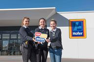 Drei Mädchen, Lehrlinge von HOFER, halten die Aufschrift