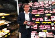 Thomas Reiter, Regionalverkaufsleiter, steht vor der Fleischabteilung und hält eine Packung abgepackte Fleischstücke vor die Kamera.