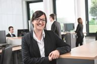 Eine Frau mit Brille und Blazer sitzt an einem Tisch im Büro und lächelt in die Kamera.