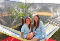 Zwei Damen sitzen entspannt auf einer Hängematte und lächeln in die Kamera.