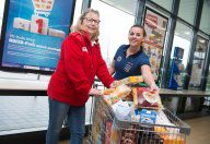 HOFER Mitarbeiterin mit Mitarbeiterin Rotes Kreuz und vollem Einkaufswagen