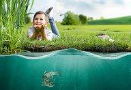 Kind auf Wiese vor Gewässer