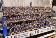Viele Menschen in blauer Kleidung sitzen auf einer HOFER-Tribüne zum Tiroler Firmenlauf.