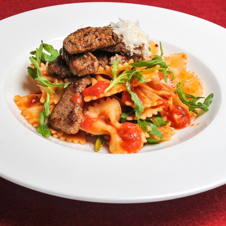 Farfalle mit Tomaten-Rucola-Sauce und gebratenen Lammstreifen