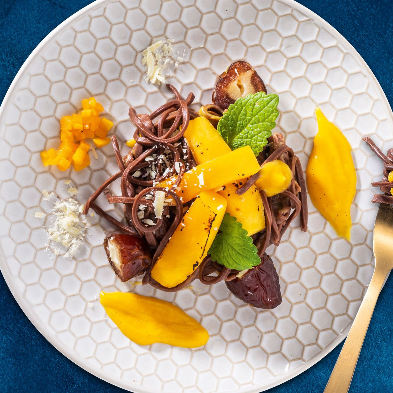 Schokopasta mit Pfirsichcreme, karamellisierte Mangospalten und Medjoul Datteln