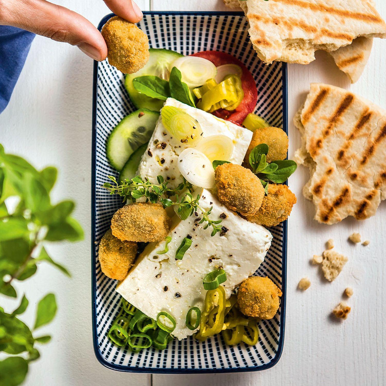Gebackene Oliven auf mariniertem Feta mit getoastetem Pitabrot
