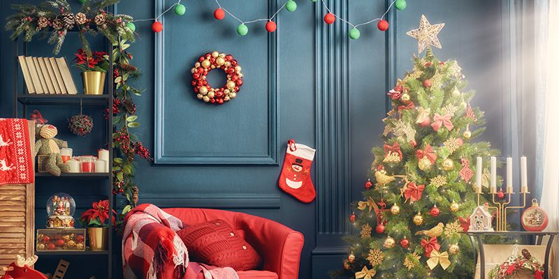 Weihnachtsdeko wie eine rote Socke, geschmückte Tannenzweige und ein Adventkranz hängen oder stehen vor einer blauen Wand.