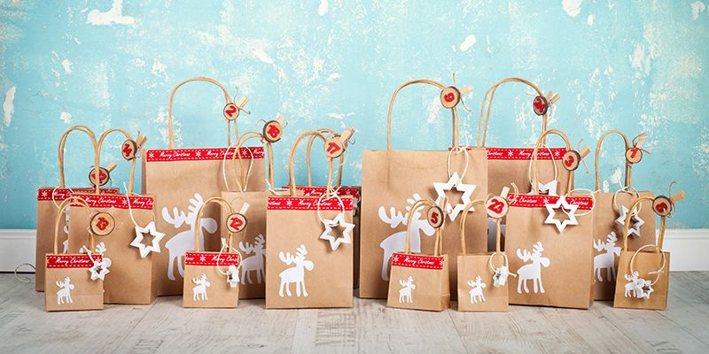 Selbstgebastelter Adventkalender aus Papiertüten mit Rentieren darauf, die für jeden Tag eine Nummer haben.