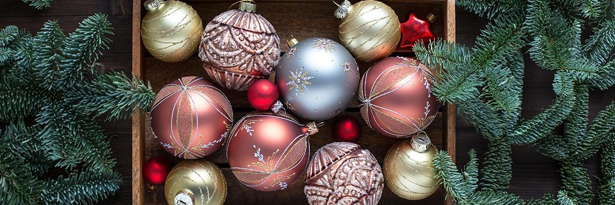 Sehr fein verzierte Christbaumkugeln in Rosa, Blau und Gold liegen in einer Holzkiste, daneben sind Tannenzweige.