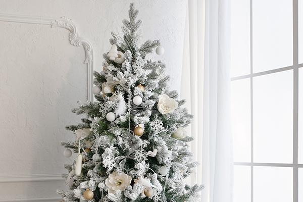 Ein vollgeschmückter Weihnachtsbaum in weiß und Silber vor einer weißen Wand.