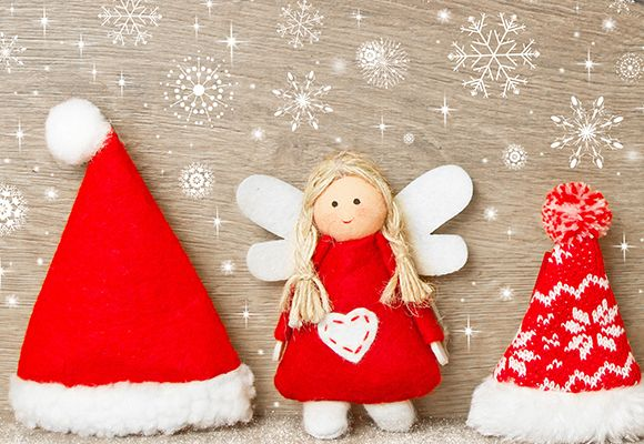 Zwei genähte Christkinder in rot und weiß gekleidet, stehen zwischen roten Zipfelmützen.