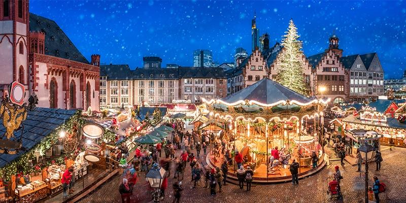 Draufsicht eines klassischen Christkindlmarktes mit vielen Lichtern, Ständen und Christbaum inmitten einer Altstadt.