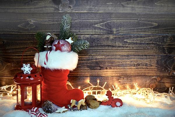 Ein roter Nikolausschuh gefüllt mit Tannenzweigen, Nüssen und Zuckerstangen, steht neben einer leuchtenden Kerze auf Schnee.