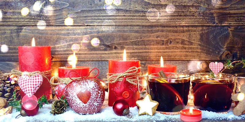 Vier unterschiedlich hohe, rote Kerzen brennen. Davor stehen Plätzchen und Glühwein.