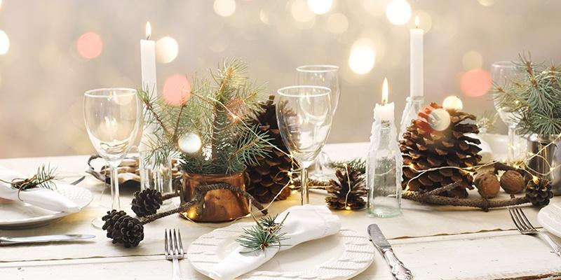 Ein festlich Gedeckter Tisch in Weiß mit leeren Weingläsern, Tannenzweigen, Tannenzapfen und Kerzen in kleinen Flaschen.