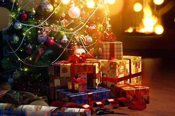 Bunt eingepackte Weihnachtsgeschenke liegen vor einem geschmückten Weihnachtsbaum bei festlicher Beleuchtung.