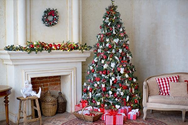 Ein altmodisches Zimmer mit Kamin und Sofa, in dem ein rot-weiß geschmückter Christbaum mit Geschenken steht.