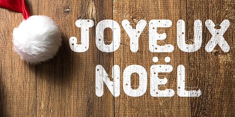 """Frohe Weihnachten auf französisch """"Joyeux Noel"""" mit weißer Farbe auf Holz gemalt, links daneben eine glänzende Weihnachtsmütze."""