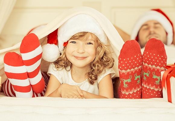 Ein Mädchen mit blonden Locken trägt eine Weihnachtsmütze während Füße in Weihnachtssocken links und rechts von ihr liegen.