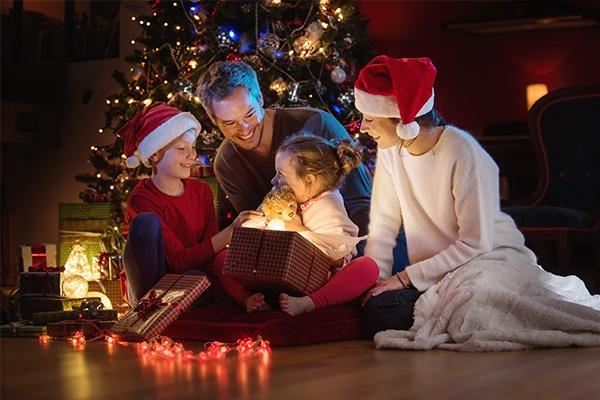 Eine vierköpfige Familie trägt teilweise Weihnachtsmützen und überreicht gemeinsam ein Geschenk an die Kinder.
