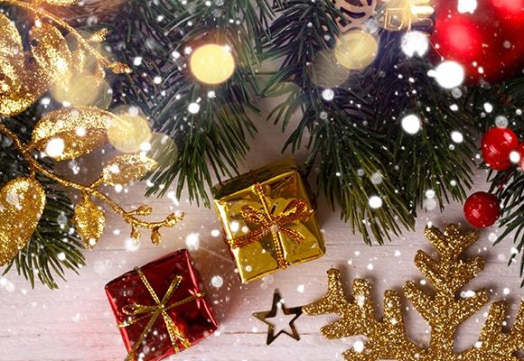 Tannenzweige geschmückt mit goldener und roter Weihnachtsdekoration aus Kugeln und Geschenkpäckchen. Es schneit.