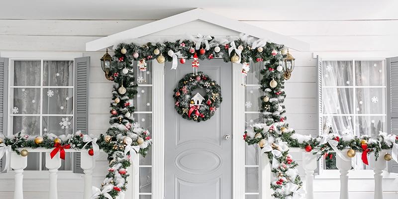 Klassische Weihnachtsdekoration mit Tannenzweigen, Christbaumschmuck und Adventkranz an einer weiß-grauen Haustür von außen.
