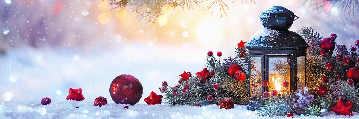Rot geschmückte Tannenzweige liegen neben einer brennenden Kerze im Schnee.